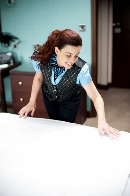 A maid cleaning  the bed